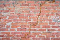 Abstrakte rote gebrochene Backsteinmauerbeschaffenheit mit großem Sprung in der Mitte Stockfotos