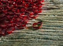 Abstrakte rote Herzform des Geschenkbandes auf hölzerner Beschaffenheit mit schönem Licht des Sonnenglanzes Stockfoto