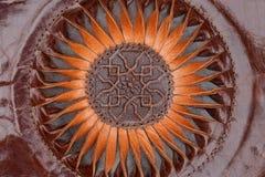 Abstrakte Sonne oder Blumenverzierung schnitzten braunes ethnisches Leder Stockbilder