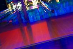 Abstrakte undeutliche Bowlingbahn mit einer Mädchenstellung Stockbild