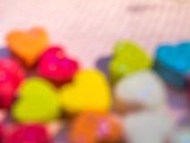 Abstrakte undeutliche mehrfarbige Herzen formen auf rosa Hintergrund Lizenzfreie Stockbilder