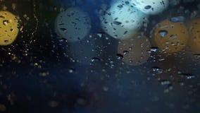 Abstrakte Unschärfeverkehrsbeleuchtung im Regen Stockfoto