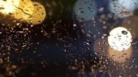 Abstrakte Unschärfeverkehrsbeleuchtung im Regen Stockfotografie