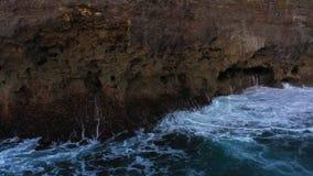 Abstrakte Vogelperspektive von den Meereswogen, die auf felsiger Küstenlinie zusammenstoßen stock video