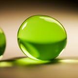 Abstrakte Zusammensetzung mit den schönen, grünen, runden Geleebällen auf einer Aluminiumfolie mit Reflexionen Lizenzfreie Stockfotografie