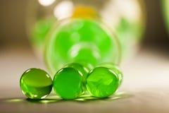 Abstrakte Zusammensetzung mit den schönen, grünen, transparenten, runden Geleebällen auf einer Aluminiumfolie mit Reflexionen Lizenzfreies Stockfoto