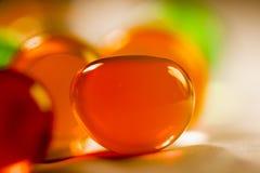 Abstrakte Zusammensetzung mit den schönen, orange, runden Geleebällen auf einer Aluminiumfolie mit Reflexionen Lizenzfreies Stockfoto