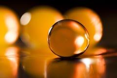 Abstrakte Zusammensetzung mit den schönen, orange, transparenten, runden Geleebällen auf einer Aluminiumfolie mit Reflexionen Stockbild