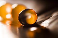 Abstrakte Zusammensetzung mit den schönen, orange, transparenten, runden Geleebällen auf einer Aluminiumfolie mit Reflexionen Lizenzfreies Stockfoto