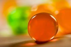 Abstrakte Zusammensetzung mit den schönen, orange, transparenten, runden Geleebällen auf einer Aluminiumfolie mit Reflexionen Lizenzfreie Stockfotografie