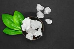 Abstrakte Zusammensetzung von grünen Blättern, hölzerne dunkle Schüssel und großer Zucker oder Salzkristalle auf grauem Hintergru stockbild
