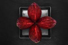 Abstrakte Zusammensetzung von vier Stücken hackte die Rote-Bete-Wurzeln, die auf Schwarzblech und schwarzen Steinhintergrund gese stockbilder
