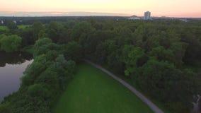 Abstrakter Architekturhintergrund Schöner Abendsee mit Sonnenuntergang im Stadtpark mit einer Ansicht von der Spitze stock footage