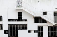 Abstrakter Außenarchitekturhintergrund - Grillfenster von verschiedenen Formen und von Größen an der weißen Betonmauer Lizenzfreie Stockfotos