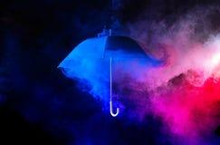Abstrakter Begriff - blauer Regenschirm unter bunten Staubwolken lizenzfreie stockbilder