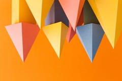 Abstrakter bunter geometrischer Formhintergrund Dreidimensionale Prismapyramidengegenstände auf orange Papier Gelbes Blau Lizenzfreie Stockfotografie
