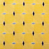 Abstrakter gelber Stoffhintergrund mit blauen Diamanten Lizenzfreie Stockfotografie