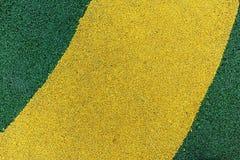Abstrakter gelber und grüner Lack auf Asphalt Stockfoto