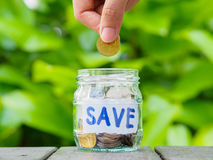 Abstrakter Geldeinsparungs-Handgriff und gesetzte Münze zum Glasgefäß Stockfotografie