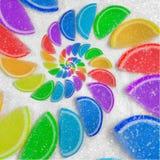 Abstrakter gewundener Fruchtgeleeregenbogen zwängt Scheiben auf Sandhintergrund des raffinierten Zuckers Regenbogengeleesüßigkeit stockbild
