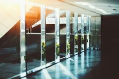 Abstrakter Glas- und Chrombüroinnenhintergrund mit Sonnenra Stockfoto
