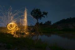 Abstrakter Hintergrund von spinnender Stahlwolle auf Klippe nachts t Stockbilder
