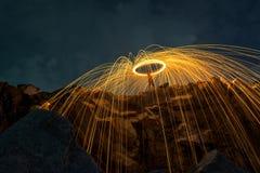 Abstrakter Hintergrund von spinnender Stahlwolle auf Klippe nachts t Stockfotografie