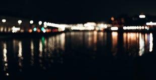 Abstrakter Hintergrund von unscharfen Stadtlichtern mit bokeh Effekt reflektiert auf Wasser lizenzfreies stockbild