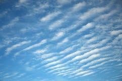 Abstrakter Hintergrund von weißen gewellten Wolken auf einem hellen blauen Himmel Stockbild