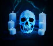 Abstrakter künstlerischer verfluchter Schädel umgeben durch Kerzen auf einem cyan-blauen Netz Hintergrund lizenzfreie stockbilder