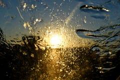 Abstrakter Regen auf Glas beim Fahren nach Westen in den Sonnenuntergang Lizenzfreie Stockbilder