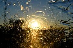 Abstrakter Regen auf Glas beim Fahren nach Westen in den Sonnenuntergang Lizenzfreie Stockfotografie