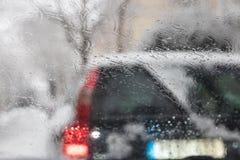 Abstrakter Regenhintergrund Regen fällt auf Autowindschutzscheibe mit Rot lizenzfreie stockbilder