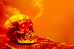 Abstrakter Schädel im orange Ton mit glänzendem Licht und Rauche des Auges Stockfoto