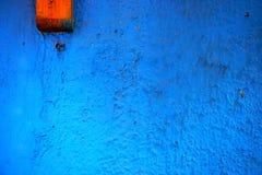 Abstrakter Schmutzhintergrund - raue blaue Wand mit einem hölzernen Block Stockbilder