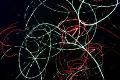 Abstrakter schwarzer Hintergrund mit chaotischen gewundenen Neonlinien Stockfoto