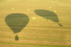 Abstrakter Spaß, Heißluft-Ballon-Schatten auf Hay Field stockfoto