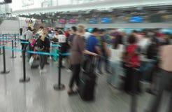 Abstrakter Unschärfe-Hintergrund, Flughafen-Abfertigungsschalter mit vielen Passagieren in der Reihe mit Bokeh Stockbilder