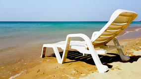 Abstrakter weißer Lehnsessel auf dem nassen Strand in der sonnigen Zeit Stockbild