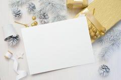 Abstrakter Weihnachtshintergrund, weißes Blatt Papier liegend unter kleinen Dekorationen auf weißem hölzernem Schreibtisch Flache lizenzfreie stockfotografie