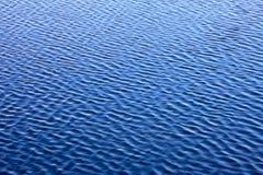 Abstrakter Wellenwasserhintergrund Goldene Kräuselungen im Wasser Stockfotos