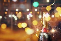 Abstraktes Bild der Sektflasche und der festlichen Lichter Lizenzfreie Stockfotos