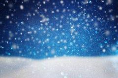 abstraktes Bild des Fliegenschnees über dunkelblauem Hintergrund, Wintersaison Stockbilder