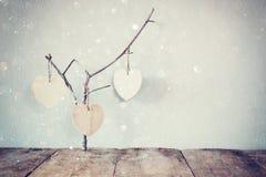 Abstraktes Bild des Hängens von hölzernen Herzen über hölzernen Hintergrund Lizenzfreie Stockfotos
