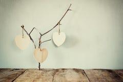 Abstraktes Bild des Hängens von hölzernen Herzen über hölzernen Hintergrund Stockbild