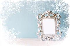 Abstraktes Bild des klassischen Rahmens der Weinleseantike auf Holztisch mit Schneeflockenüberlagerung Stockfoto
