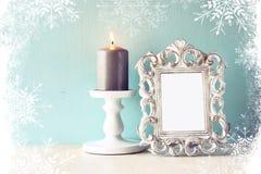 Abstraktes Bild des klassischen Rahmens der Weinleseantike und brennende Kerze auf Holztisch mit Schneeflockenüberlagerung Lizenzfreie Stockbilder
