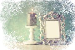 Abstraktes Bild des klassischen Rahmens der Weinleseantike und brennende Kerze auf Holztisch mit Schneeflockenüberlagerung Lizenzfreie Stockfotografie