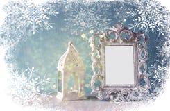 Abstraktes Bild des klassischen Rahmens der Weinleseantike und der alten Laterne auf Holztisch mit Schneeflockenüberlagerung Lizenzfreies Stockfoto