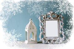 Abstraktes Bild des klassischen Rahmens der Weinleseantike und der alten Laterne auf Holztisch mit Schneeflockenüberlagerung Lizenzfreie Stockfotografie
